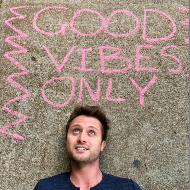 Vinnie Schieder laying on concrete looking up at the words Good Vibes Only written on the ground with sidewalk chalk