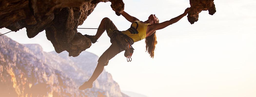 mountain climber woman climbing up a mountain