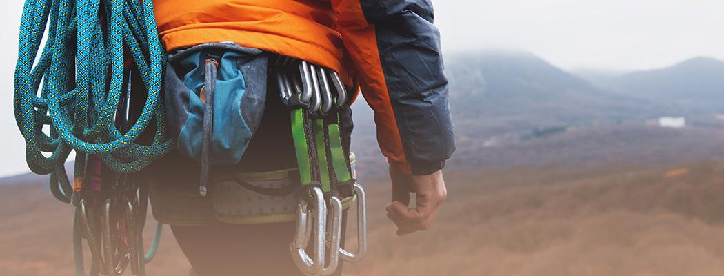 mountain climber hiker walking toward a mountain wearing climbing gear
