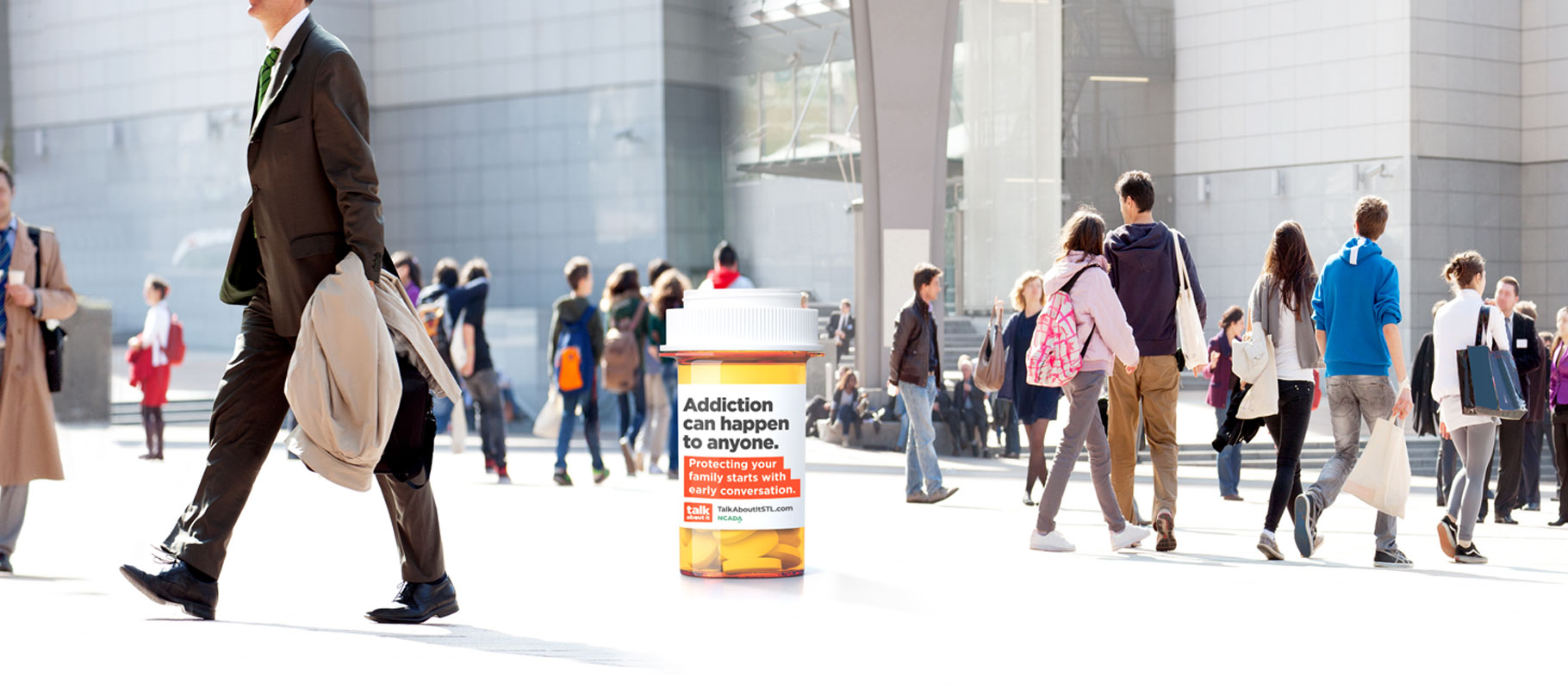 Talk About It pill bottle in the middle of a public space with people walking around it